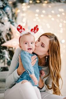 Baby mit mutter auf boden nahe weihnachtsbaum. frohes neues jahr und frohe weihnachten.