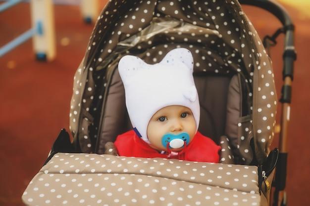 Baby mit schnuller im mund im kinderwagen