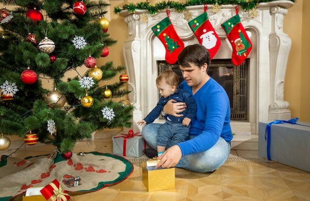 Baby mit seinem vater öffnet weihnachtsgeschenke auf dem boden im wohnzimmer
