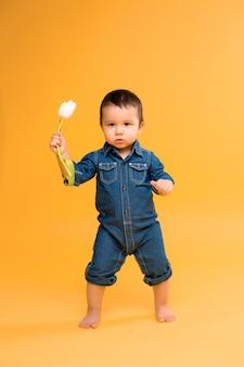 Baby mit tulpe auf gelbem hintergrund