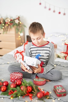 Baby mit weihnachtsgeschenken zu hause auf bett mit weihnachtsdekor