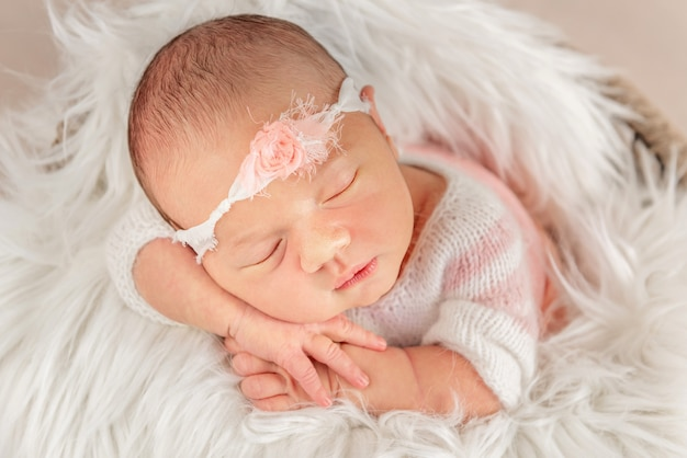 Baby mit weißem stirnband in weicher decke