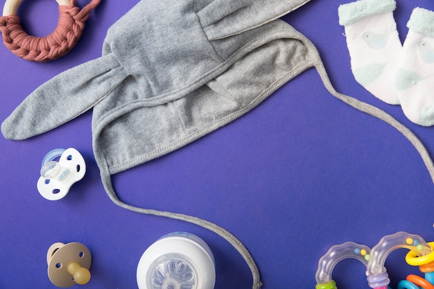 Baby mütze mit schnuller; milchflasche; spielzeug und paar socken auf blauem hintergrund