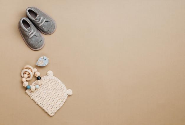 Baby-naturmaterial-zubehörkonzept. baby-beißring aus holz, strickmütze und schuhe auf beigem hintergrund mit leerzeichen für text. draufsicht, flach liegen.