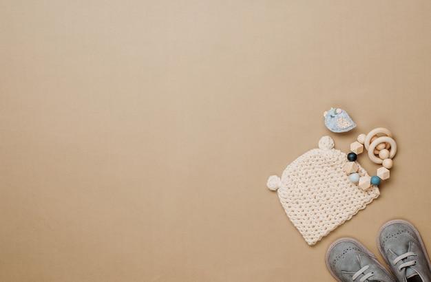 Baby-naturmaterial-zubehörkonzept. beißring aus holz, strickmütze und schuhe auf beigem hintergrund mit leerzeichen für text. draufsicht, flach liegen.