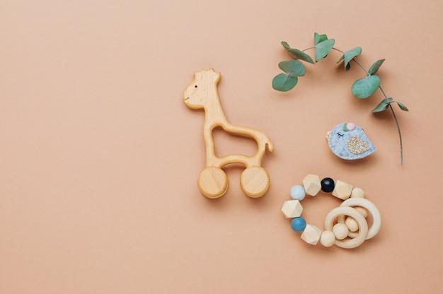 Baby-naturmaterial-zubehörkonzept. hölzerne spielzeuggiraffe und beißring auf beigem hintergrund mit leerzeichen für text. draufsicht, flach liegen.