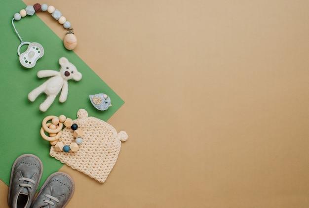 Baby-naturmaterial-zubehörkonzept. neugeborener hut und schuhe auf beigem hintergrund mit leerzeichen für text. draufsicht, flach liegen.