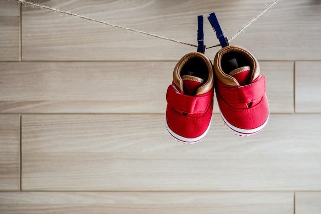 Baby-roter schuhfall auf wäscheleine und hintergrundraum für text