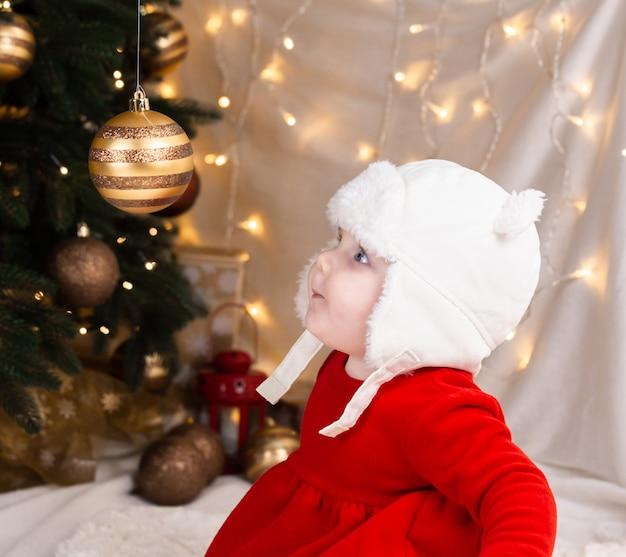 Baby schaut auf einen weihnachtsbaumball. süßes kleines mädchen in einem roten kleid und weißem hut drückt gefühle aus. weihnachtskonzept mit kleinem kind