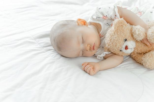Baby schläft mit einem teddybär