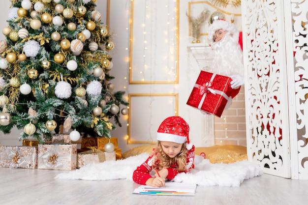 Baby schreibt einen brief, und der weihnachtsmann mit einem geschenk spioniert sie am weihnachtsbaum aus