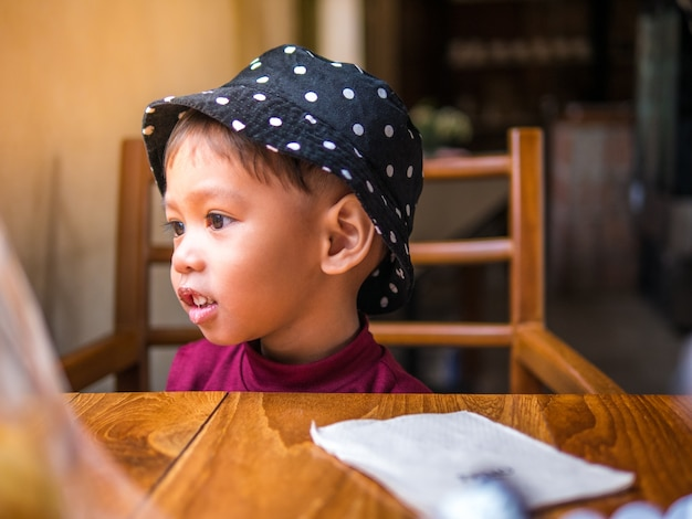 Baby-sehr spaßfamilie der fütterungsbäckerei der asiatischen mutter zu ihrer netten tochter im café.