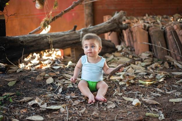 Baby sitzt auf dem hinterhof boden