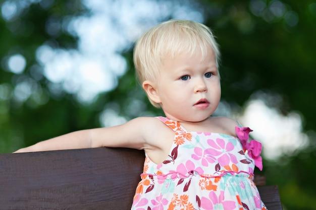 Baby sitzt auf der bank