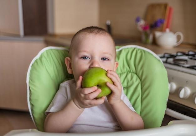 Baby sitzt auf einem stuhl und isst grünen apfel. baby isst die richtige ernährung. ökologische produkte