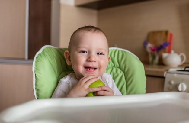 Baby sitzt auf einem stuhl und isst grünen apfel
