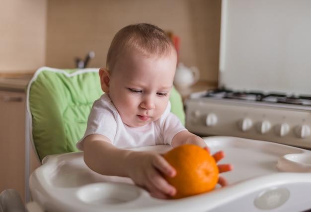 Baby sitzt auf einem stuhl und isst orange