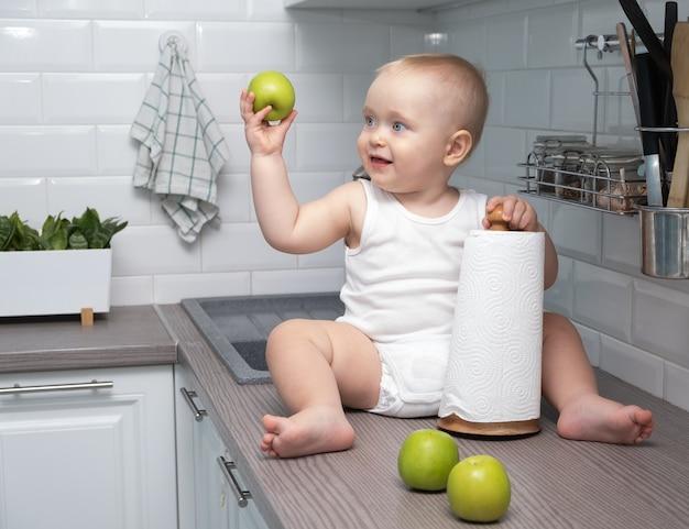 Baby sitzt in der weißen küche im haus und isst äpfel.