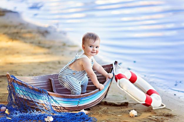 Baby sitzt in einem boot, gekleidet als seemann an einem sandstrand mit muscheln am meer