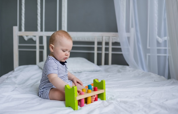 Baby sitzt in einem gestreiften overall und spielt mit einem holzspielzeug auf einem weißen bett im zimmer