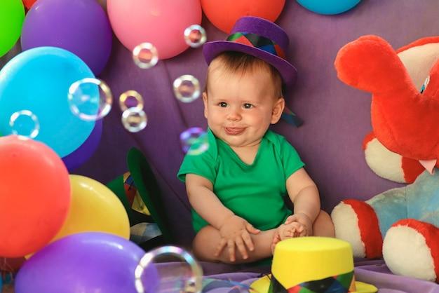 Baby sitzt in einer lustigen festlichen atmosphäre mit luftballons und beobachtet seifenblasen.