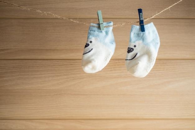 Baby-sockenfall auf hölzerner leerstelle der wäscheleine und des hintergrundes