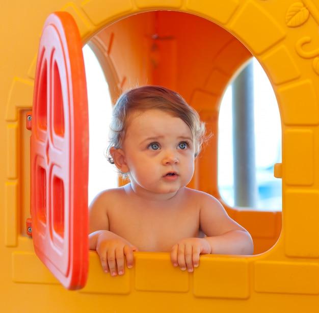Baby spielt am strand in einem miniaturhaus