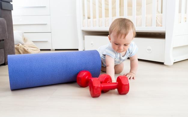 Baby spielt auf dem boden mit fitnessmatte und hanteln. konzept des kindersports