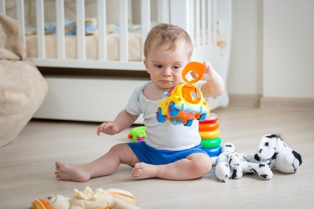 Baby spielt mit buntem spielzeugauto auf dem boden im wohnzimmer