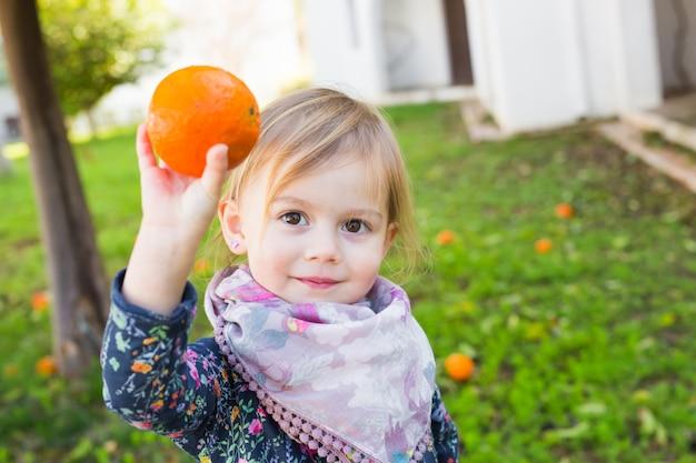 Baby spielt mit orangen. gesunde ernährung