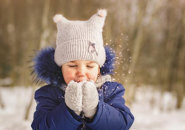 Baby spielt mit schnee im winter an einem sonnigen tag