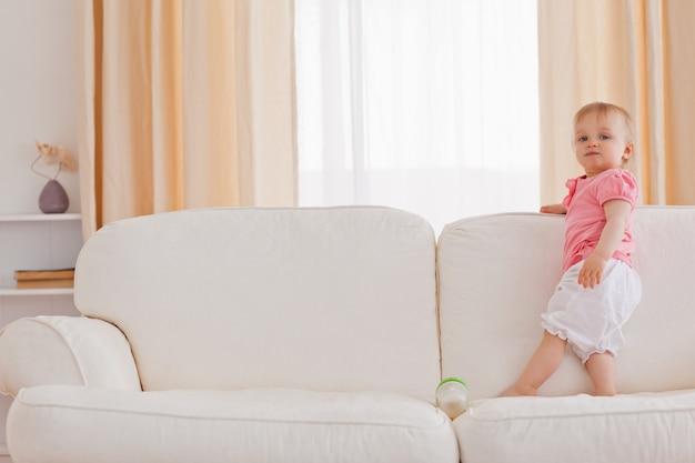 Baby steht auf einem sofa