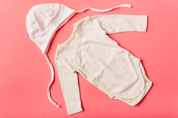 Baby-strampelanzug und kopfbedeckung kappe auf hellem hintergrund