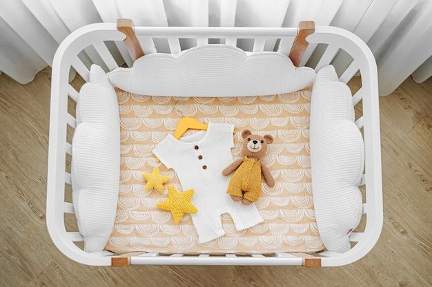 Baby strampler mit spielzeugbär für ein neugeborenes im kinderbett, wiege. weißes hölzernes babybett mit kissenförmigen wolken im babyzimmer. draufsicht auf das kinderbett
