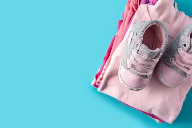Baby strampler und babyschuhe auf blauem hintergrund
