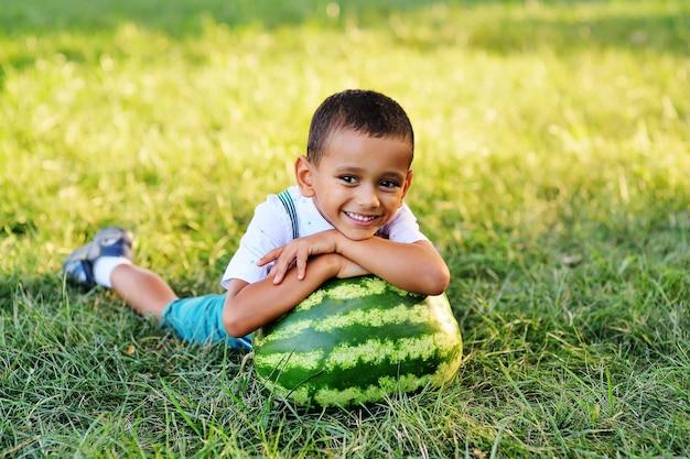 Baby-süßer schwarzer afroamerikanerjunge, der auf einer riesigen wassermelone liegt und auf einem parkhintergrund an einem sonnigen sommertag lächelt
