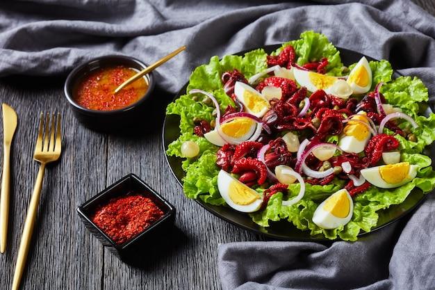 Baby-tintenfischsalat mit hart gekochten eiern, kapern, marinierten zwiebeln auf salatblättern auf einem schwarzen teller auf einem dunklen holztisch mit olivenöldressing, landschaftsansicht von oben