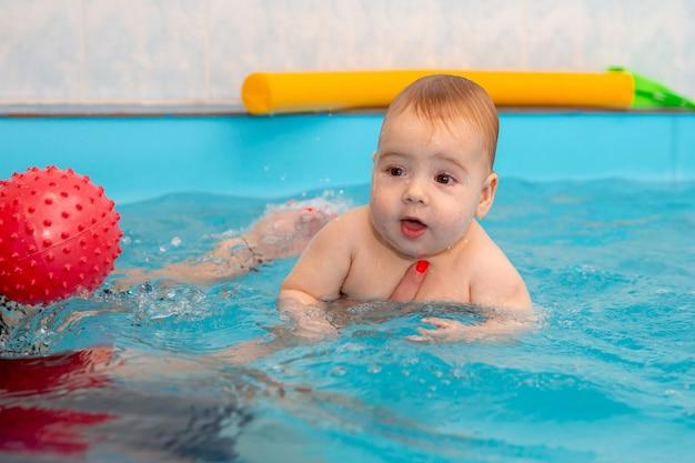 Baby trainiert, um im pool mit einem trainer zu schwimmen