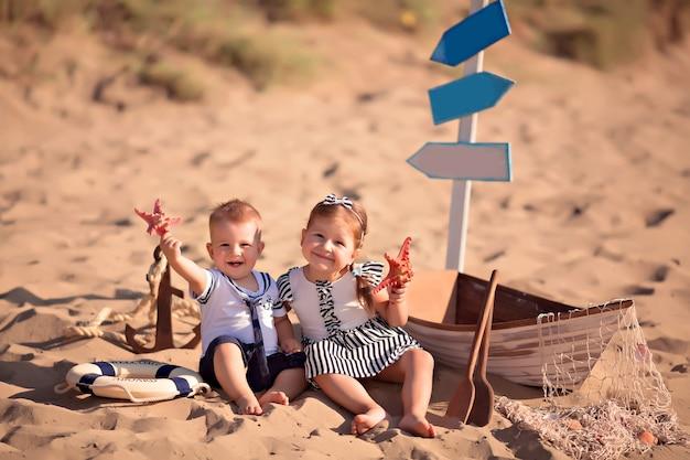 Baby und mädchen sitzen in einem boot, als seemann verkleidet, am sandstrand mit muscheln am meer
