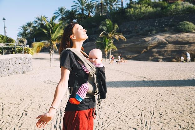 Baby und mutter auf dem meer am sommertag glückliche familie, die draußen auf der natur spazieren geht