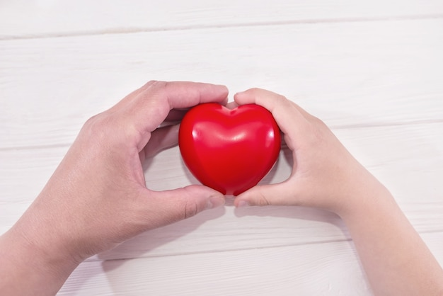 Baby- und mutterhände halten rotes herz herz krankenversicherung organspende freiwillige wohltätigkeitsorganisation soziale verantwortung für soziale verantwortung