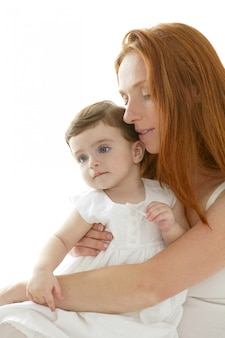Baby- und rothaarigemutter umarmen auf weiß