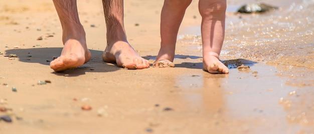 Baby und vater gehen am strand entlang