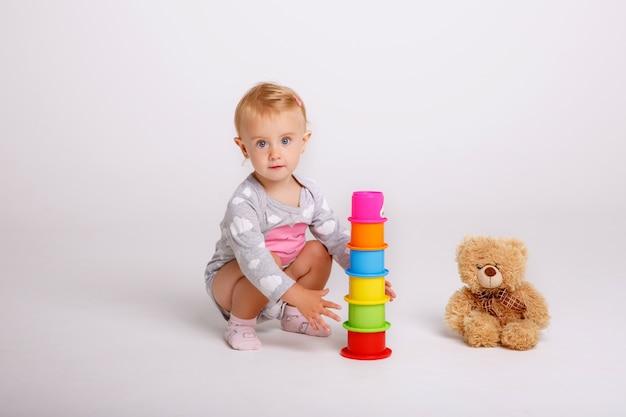 Baby, welches die spielwaren getrennt auf weiß spielt