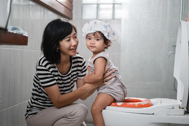 Baby welpe schaut in die kamera begleitet von einer frau mit einem toilettenhintergrund im badezimmer