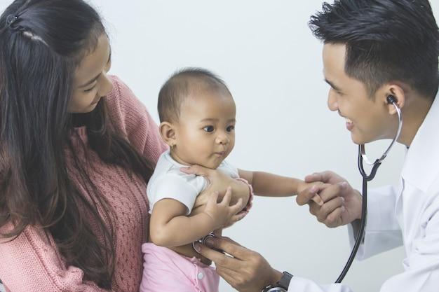 Baby wird von einem arzt untersucht