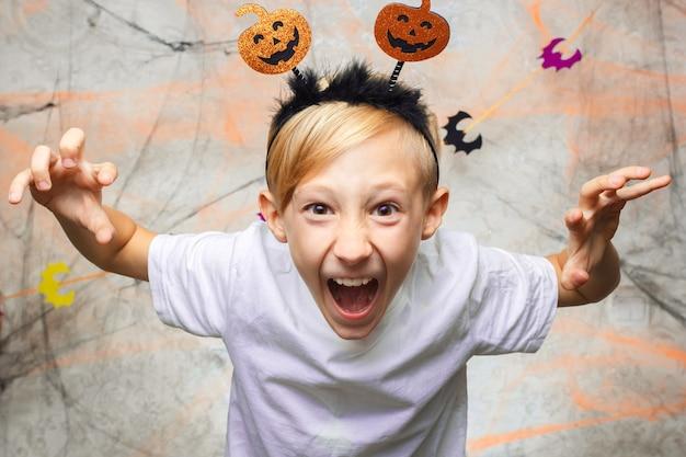 Baby zeigt lustige gesichter für die kamera an halloween