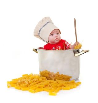 Babychef in einem riesigen topf mit nudeln