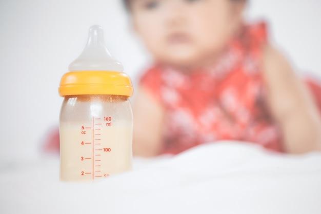 Babyflasche mit der muttermilch für das stillen auf kleinem babymädchenhintergrund.
