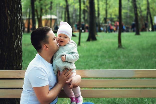 Babygirl in den armen ihres vaters auf der straße, frühling vater geht mit dem kind erste schritte der tochter